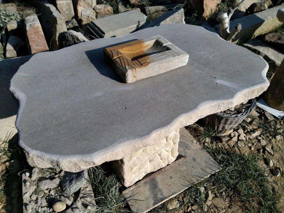 Stůl zpřírodního pískovce, který se skládá ze dvou kusů. Horní ploché desky ajedné masivní nohy.