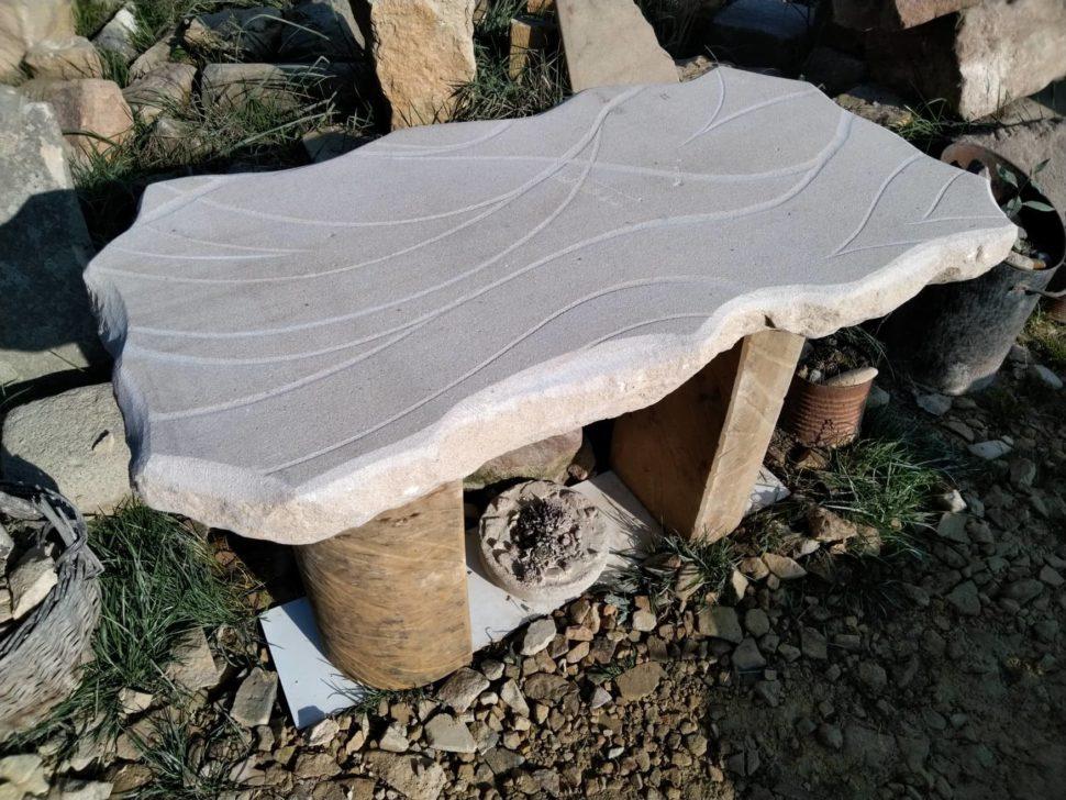 Stůl zpřírodního pískovce, který se skládá ze tří částí. Ploché desky advou nohou.