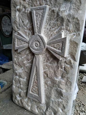 Kříž zpřírodního pískovce sbožím okem uprostřed.