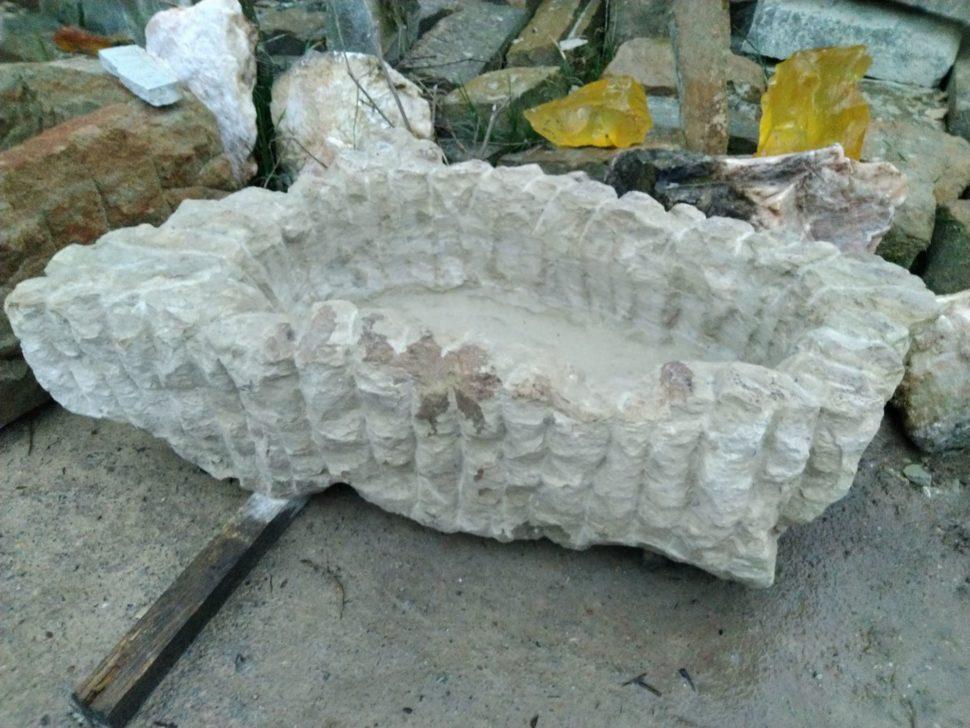 Velký vroubkovaný květináč zpřírodního pískovce ve tvaru nepravidelného obdélníku.