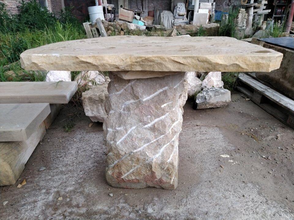 Stůl zpřírodního pískovce sjednou masitou nohou uprostřed.