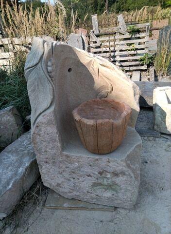 Rohová fontána zpřírodního pískovce sreliéfem hroznu avedrem imitující dřevo.