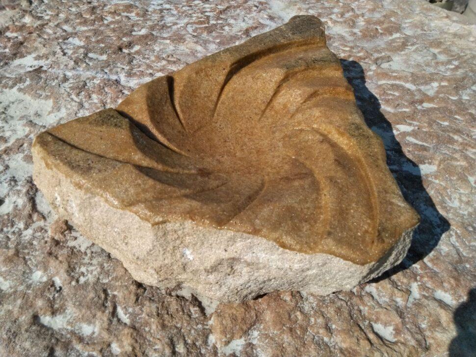 Menší pítko zpřírodního pískovce ve tvaru víru.