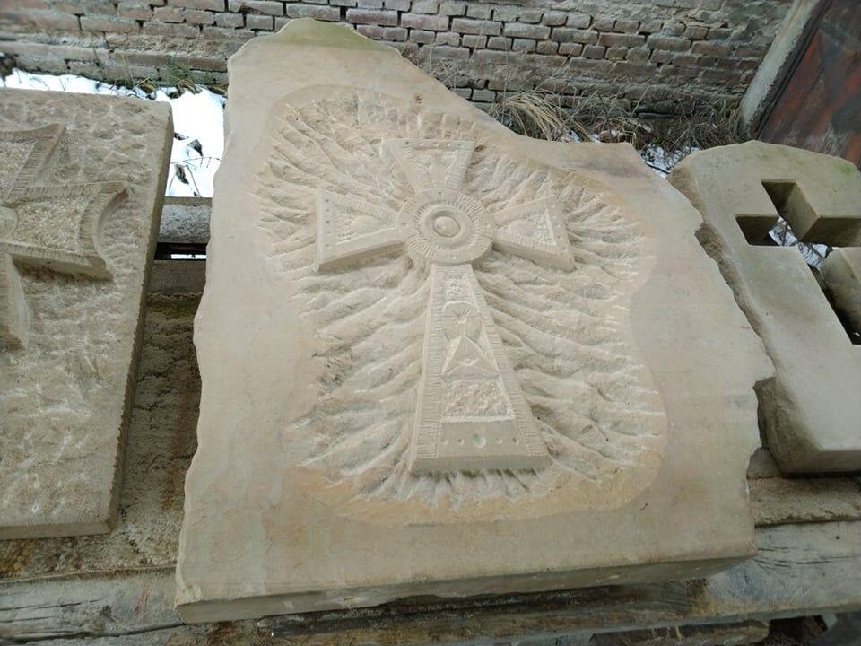 Kříž zpřírodního pískovce, který je vytvořený jako plastika nanepravidelně tvarované pískovcové desce.