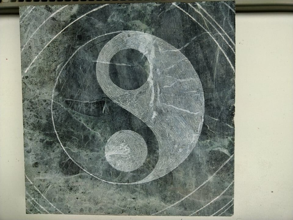 Mramorová deska se znakem jing-jang, která se dá použít jako podložka.