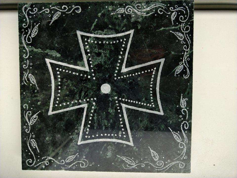 Mramorová deska se znakem maltézského kříže, která se dá použít jako podložka.