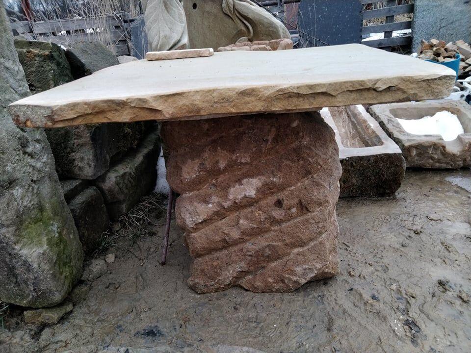 Nižší stůl najedné masivní noze zpřírodního pískovce.