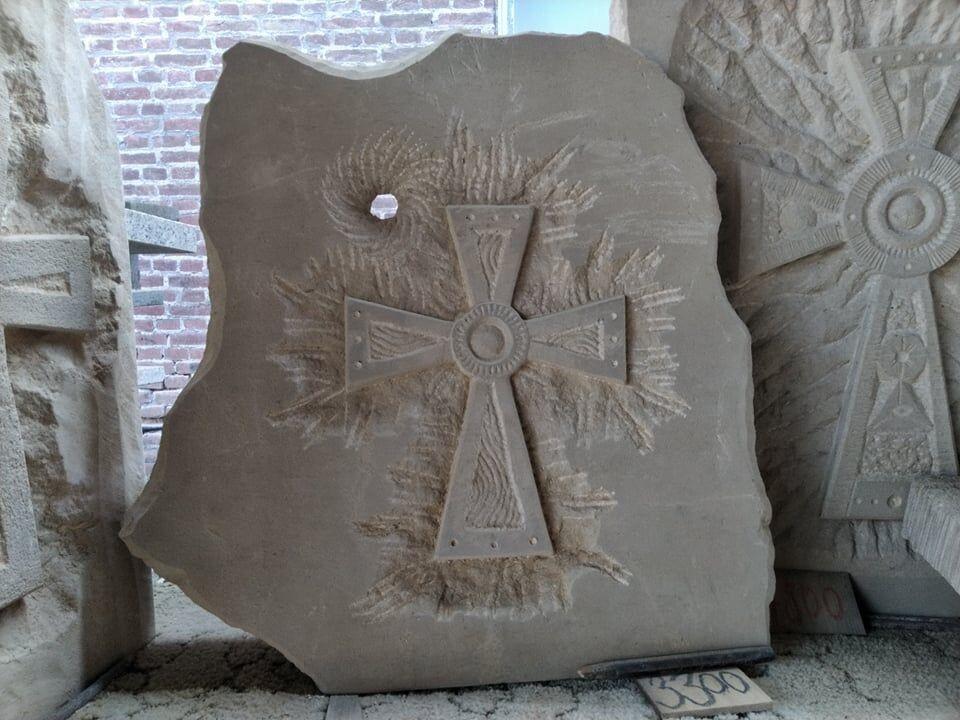 Kříž vytvořený napískovcové desce.