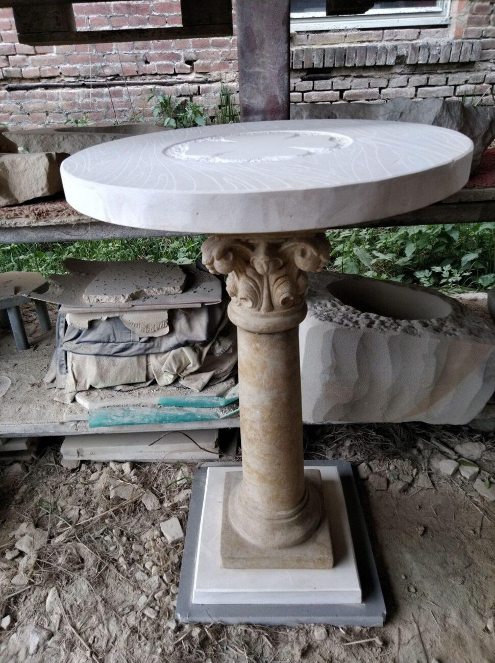 Zdobený kulatý stůl. Noha stolu je zumělého pískovce. Stolová deska apodstavec je zvápence.