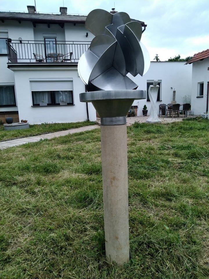 Umělecká socha kvetu znerezové oceli apodstavce zpřírodního pískovce.